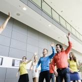 Business people dancing in the office and energizing themselves
