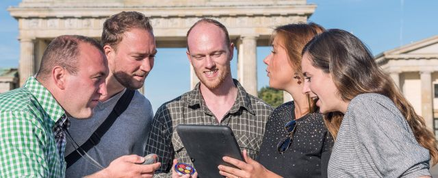 Team with an iPad in front of the Brandenburg Gate