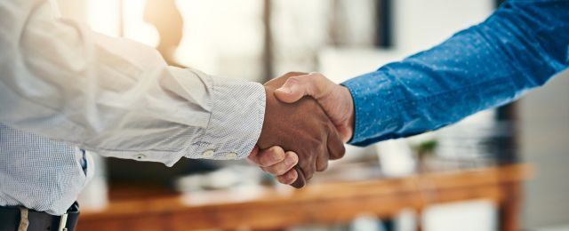 Two business partners shake hands in a business setting