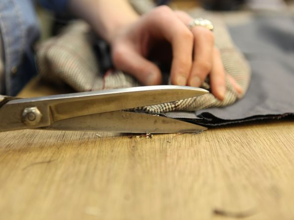 Tailor tailors made-to-measure clothing using scissors