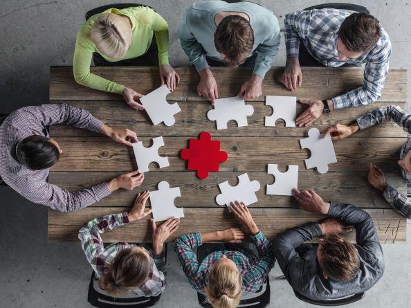 A team assembles puzzle pieces at a meeting