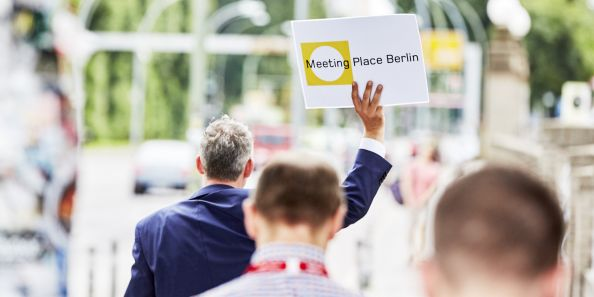 Berlin Convention Office, Service and Event Planning, One holds a sign with Meeting Place Berlin