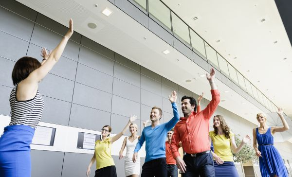 Team dances as warm-up in the office with an instructive moderator