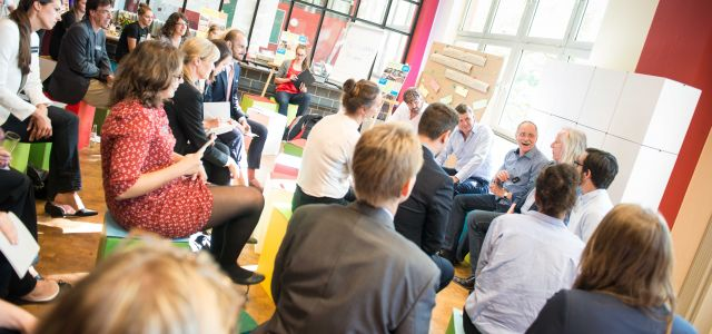 Services Berlin Convention Office, sustainable meetings in Berlin with MEET+CHANGE, participants in conference room sit on colorful cardboard stools