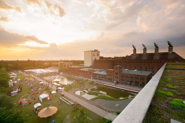 Green meadow of the event location Malzfabrik in Berlin Schöneberg at sunset.