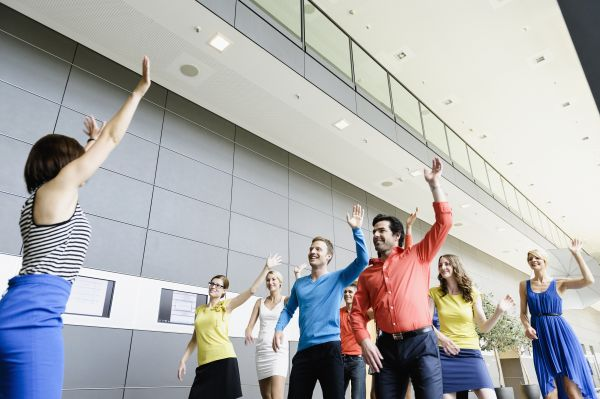 Business people dance as a warm-up in the office with a moderator